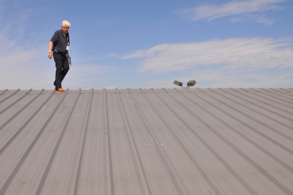 a contractor inspecting damages on a metal roof