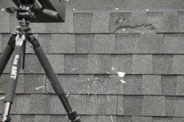 hailstone exploding on impact against shingle roof