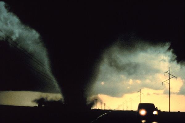 a tornado travels down a road next to a car