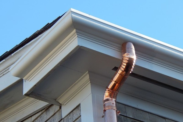 a gold-chromed downspout shining under the sun