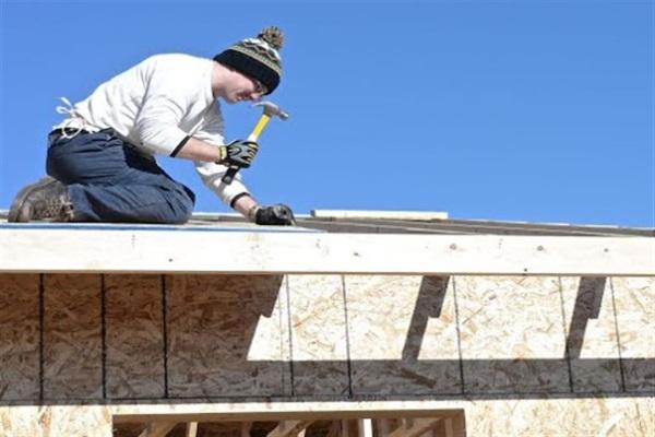 contractor finishing ridge shingle installation