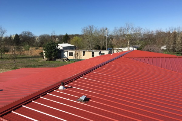 red coated metal roofing for a bungalow with a small vent
